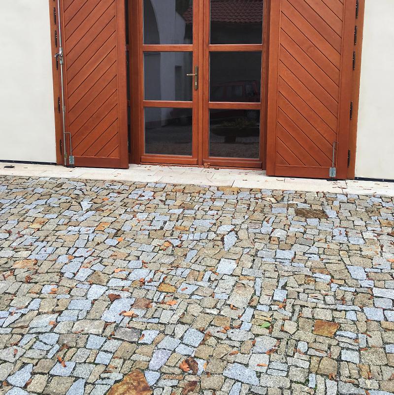 Dřevěné okenice a kamenná dlažba